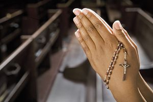 Hands Praying in Church With Rosary