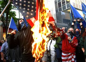 Demonstrators burn a flag