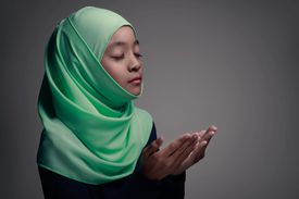 Young muslim girl praying