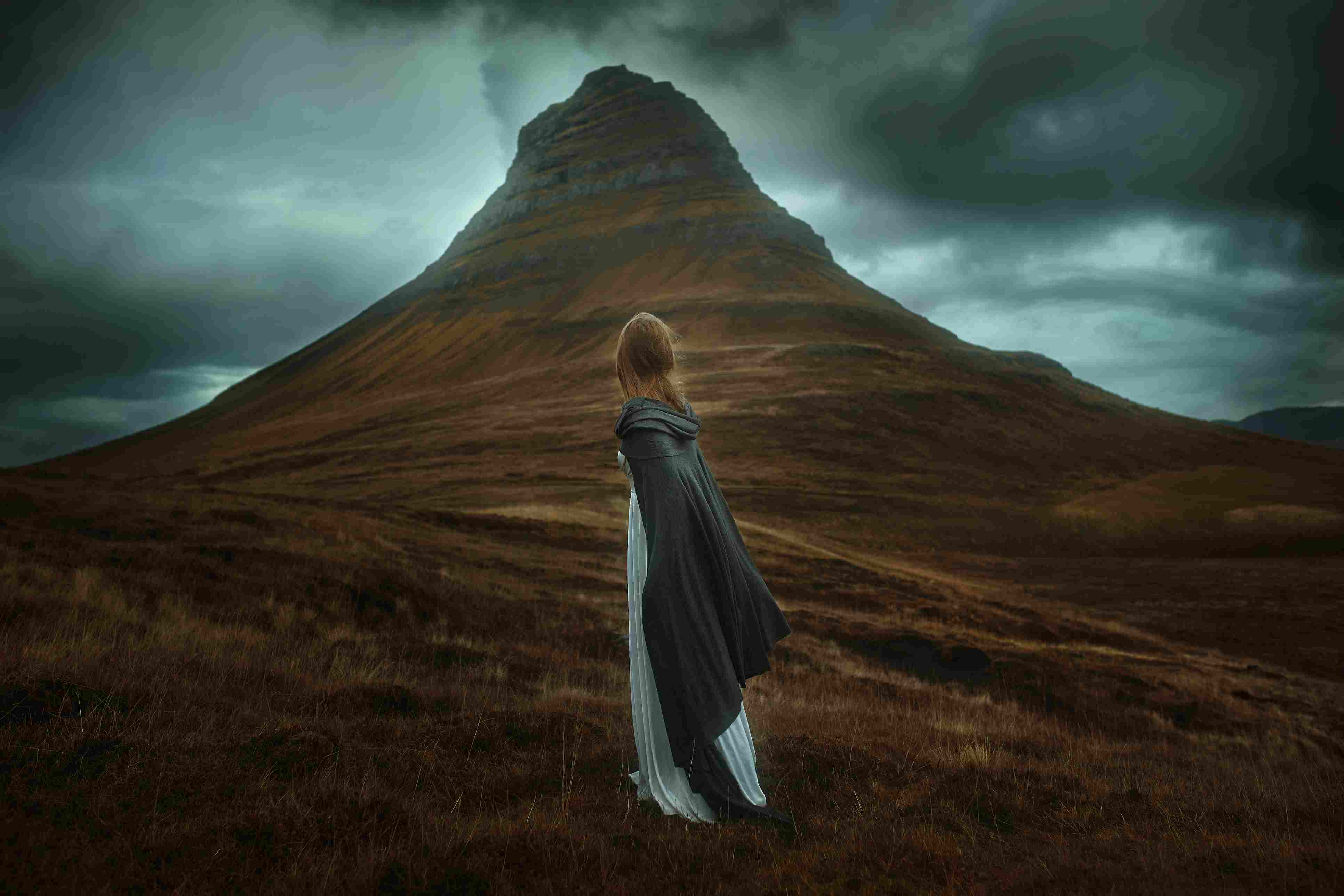 Young Woman In long dress standing in a field in Iceland