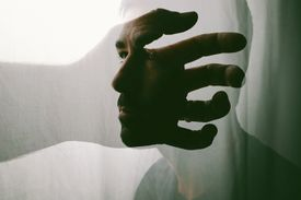 Image of a hand reaching and a man lost in thought.