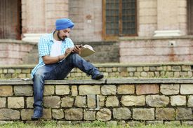 Young, turban-wearing man reading a book on stone steps.