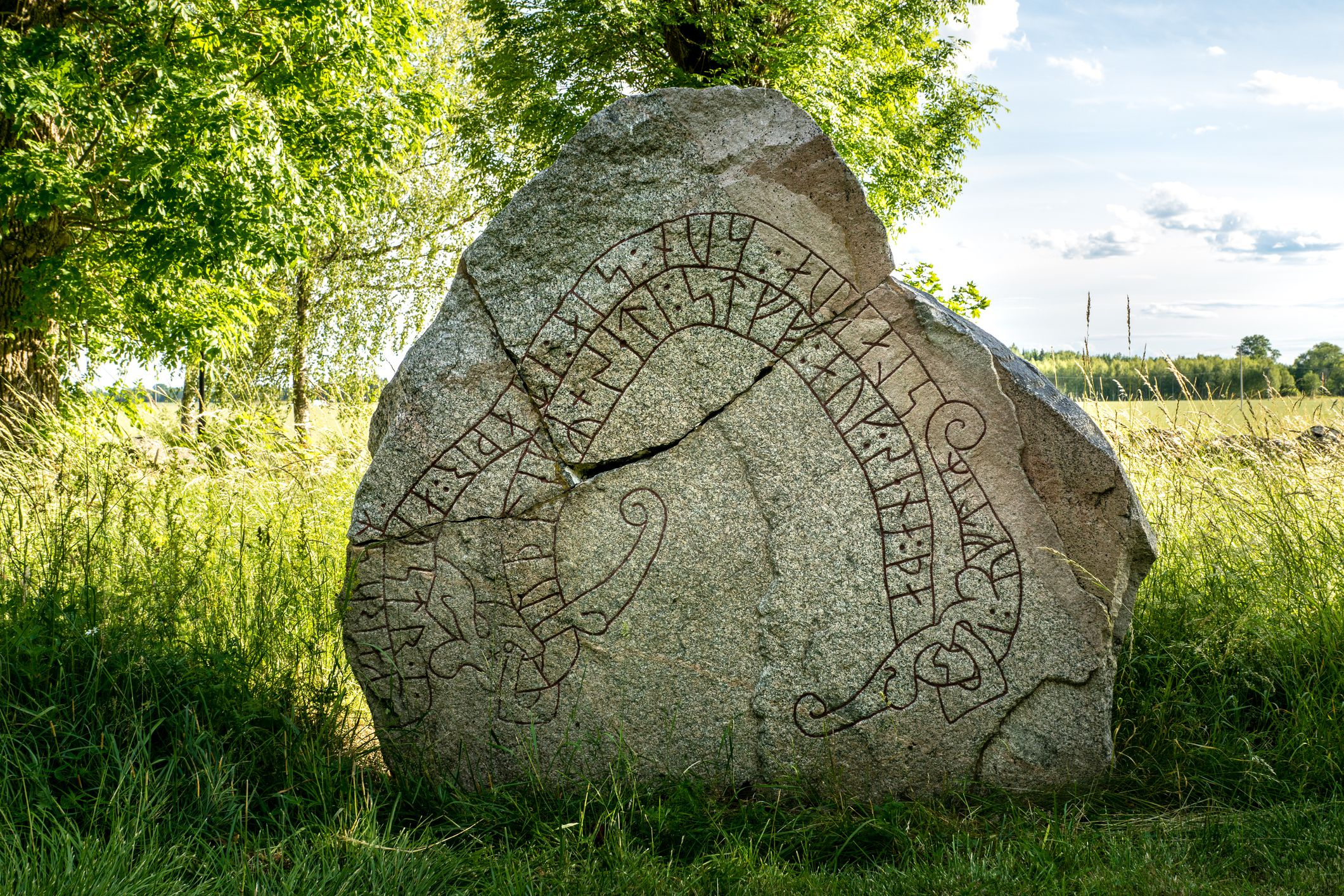 Ancient and cracked rune stone with summer background
