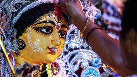 Cropped Image Of Pundit Applying Sindoor To Durga Statue During Durga Puja Festival