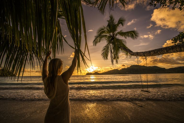 Back view of a woman looking at breathtaking sunset.