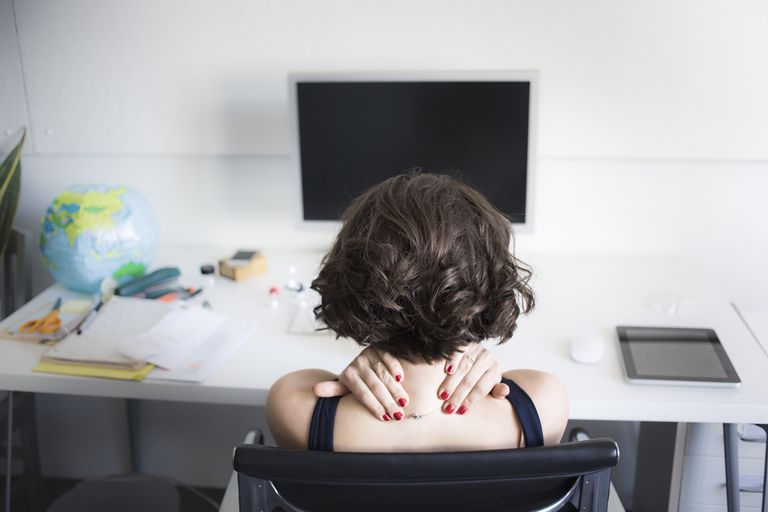 Woman massaging neck at her desk