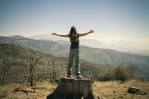 A woman standing on a tree stump, praising nature.