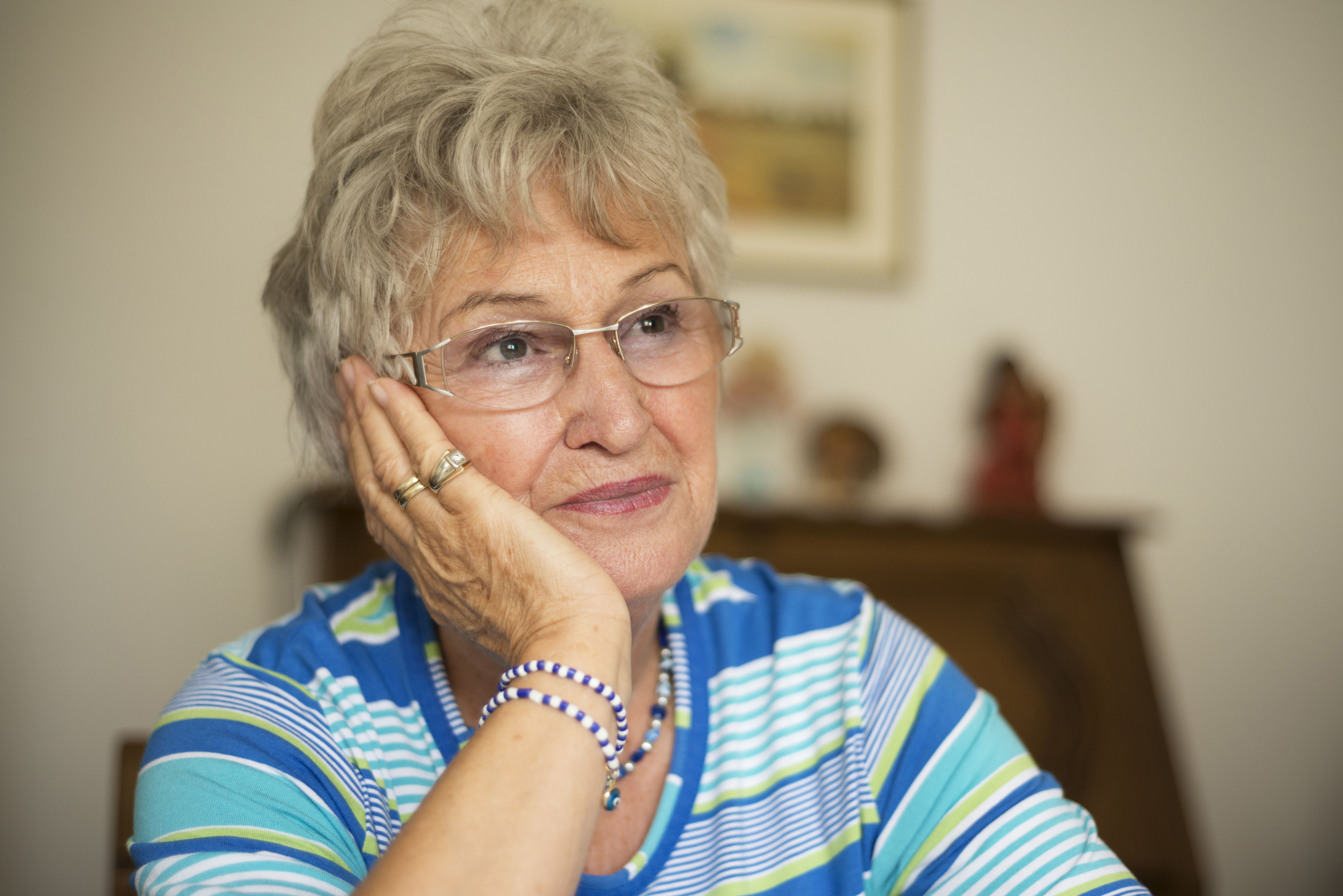Portrait of senior woman daydreaming in living room