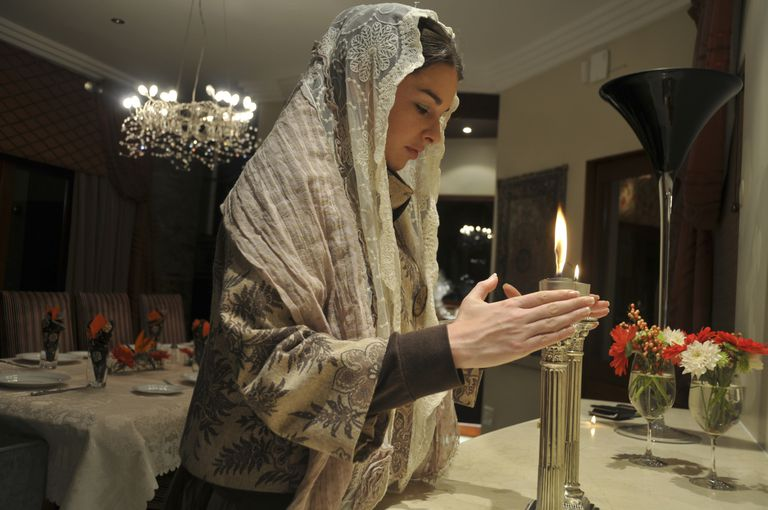 A woman lights Shabbat candles.