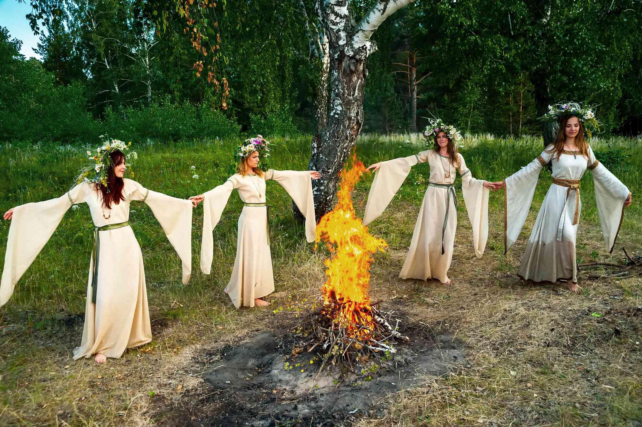 Women with flower wreath near bonfire