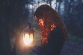 Redhead woman holding lantern at dusk