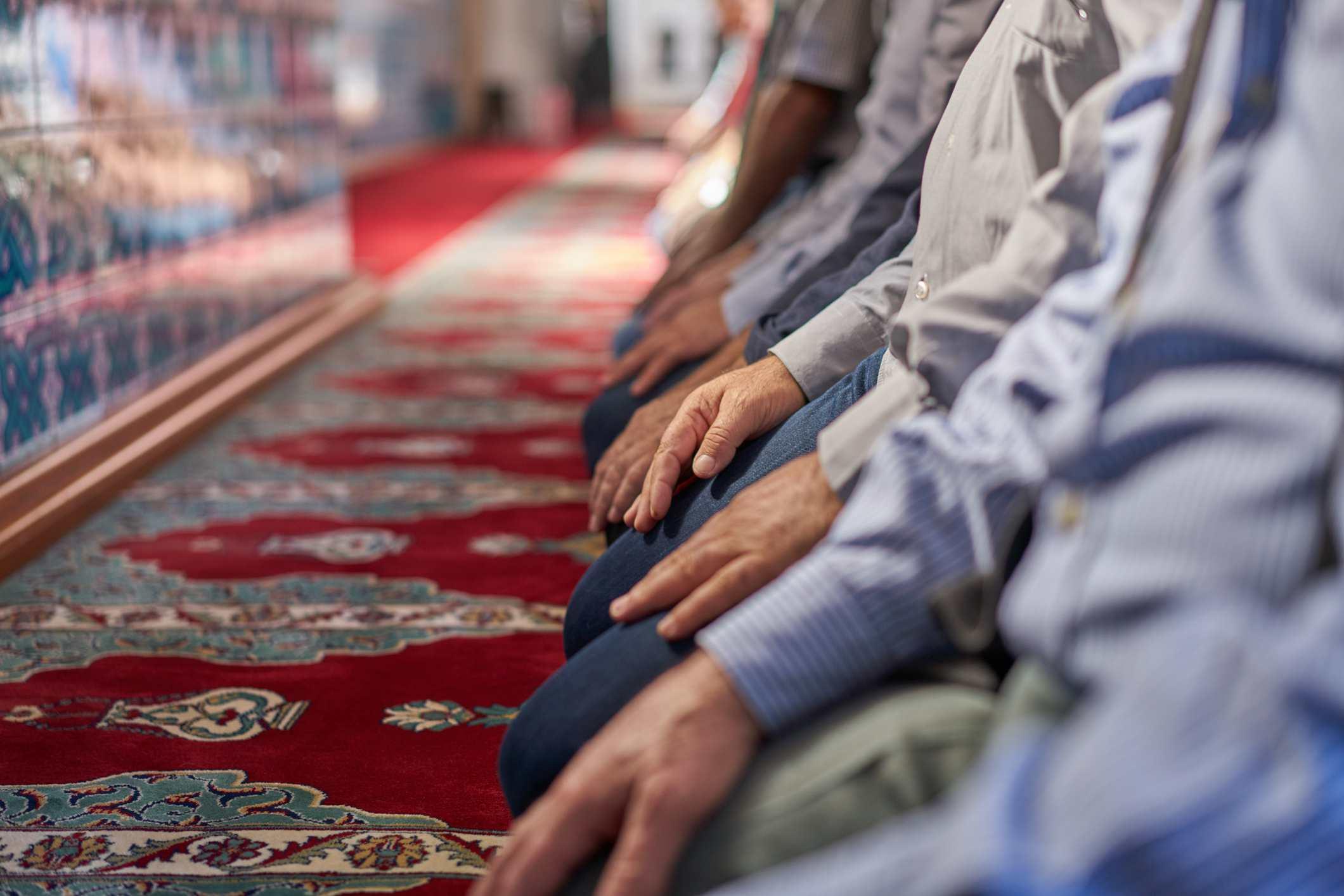 men kneeling in prayer at mosque
