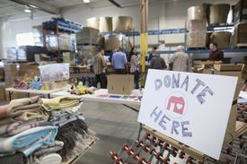 Volunteers sorting items for clothing drive in warehouse