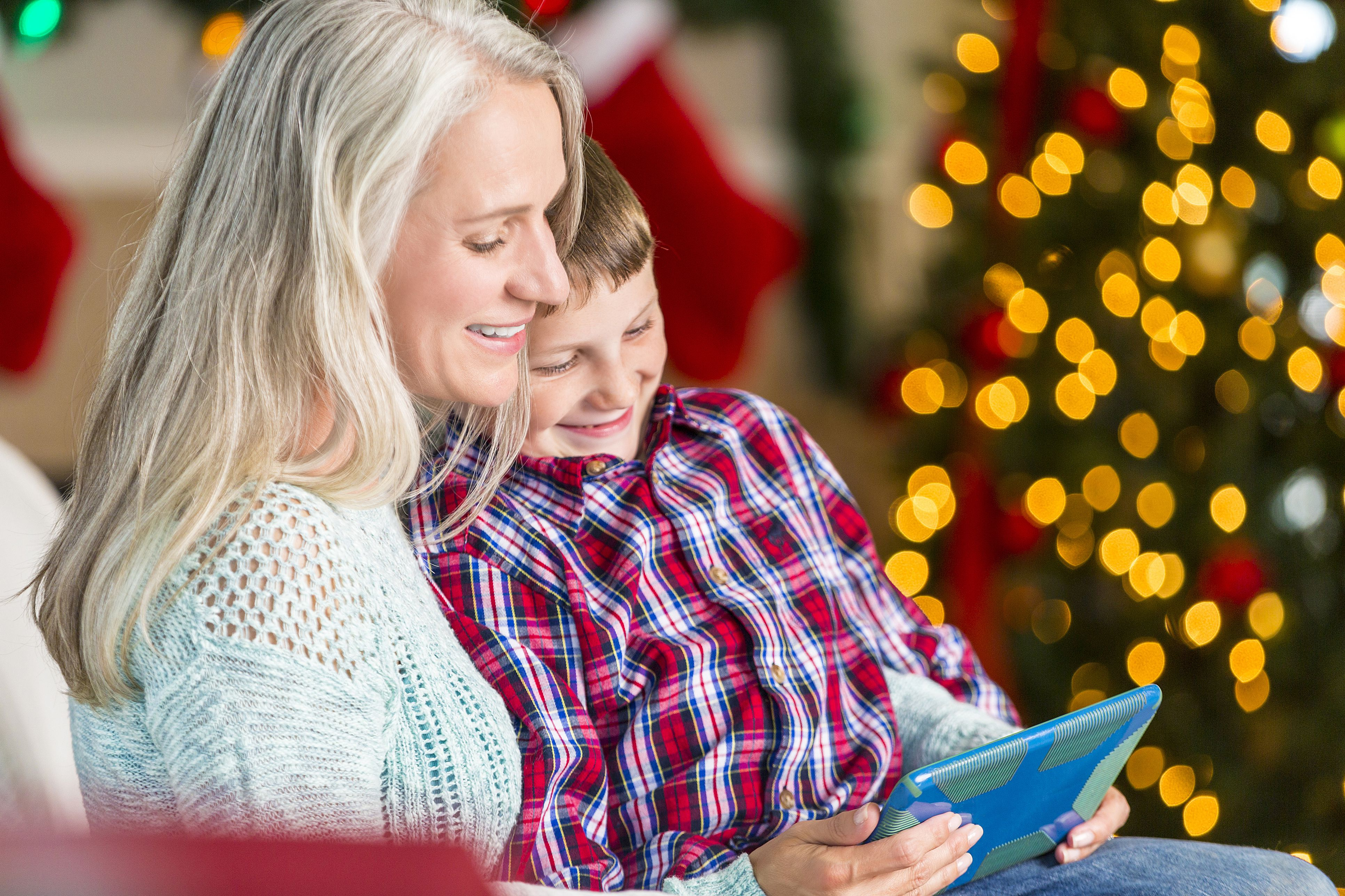 Grandmother reads story to grandson at Christmastime