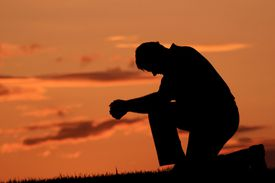 Silhouette of Middle Aged Male Saying A Prayer