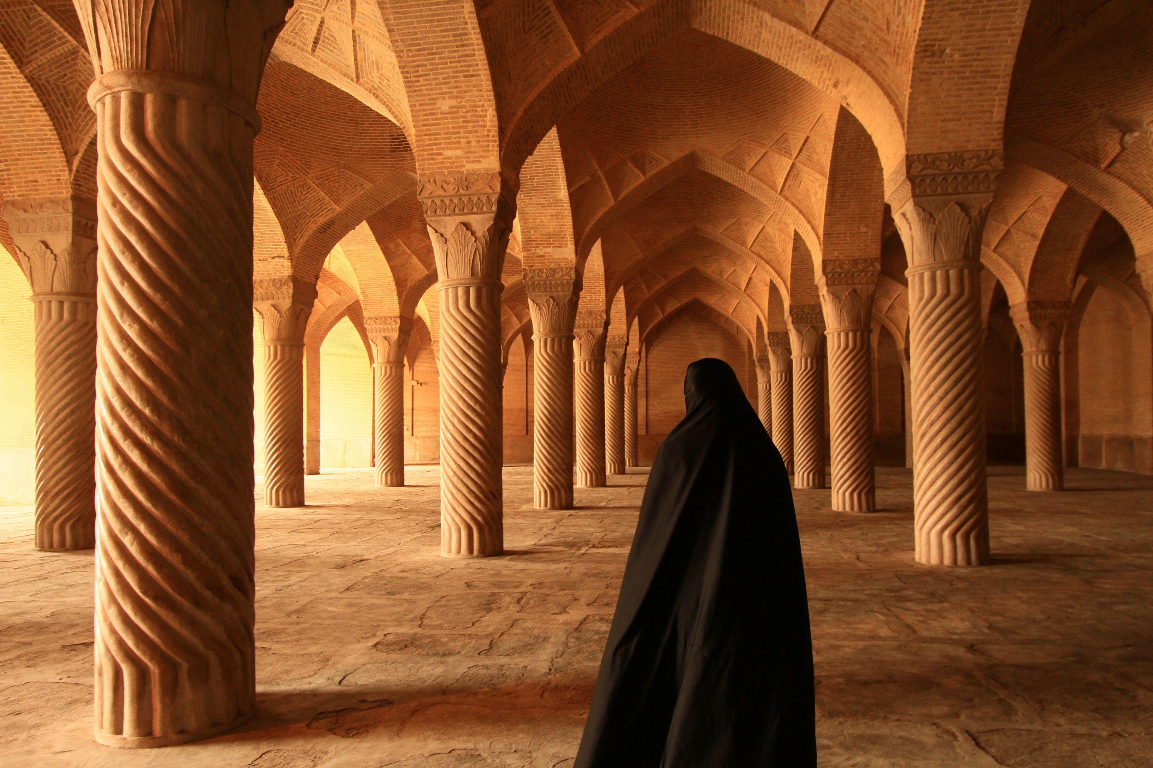 Woman in black chador in mosque in Shiraz, Iran.