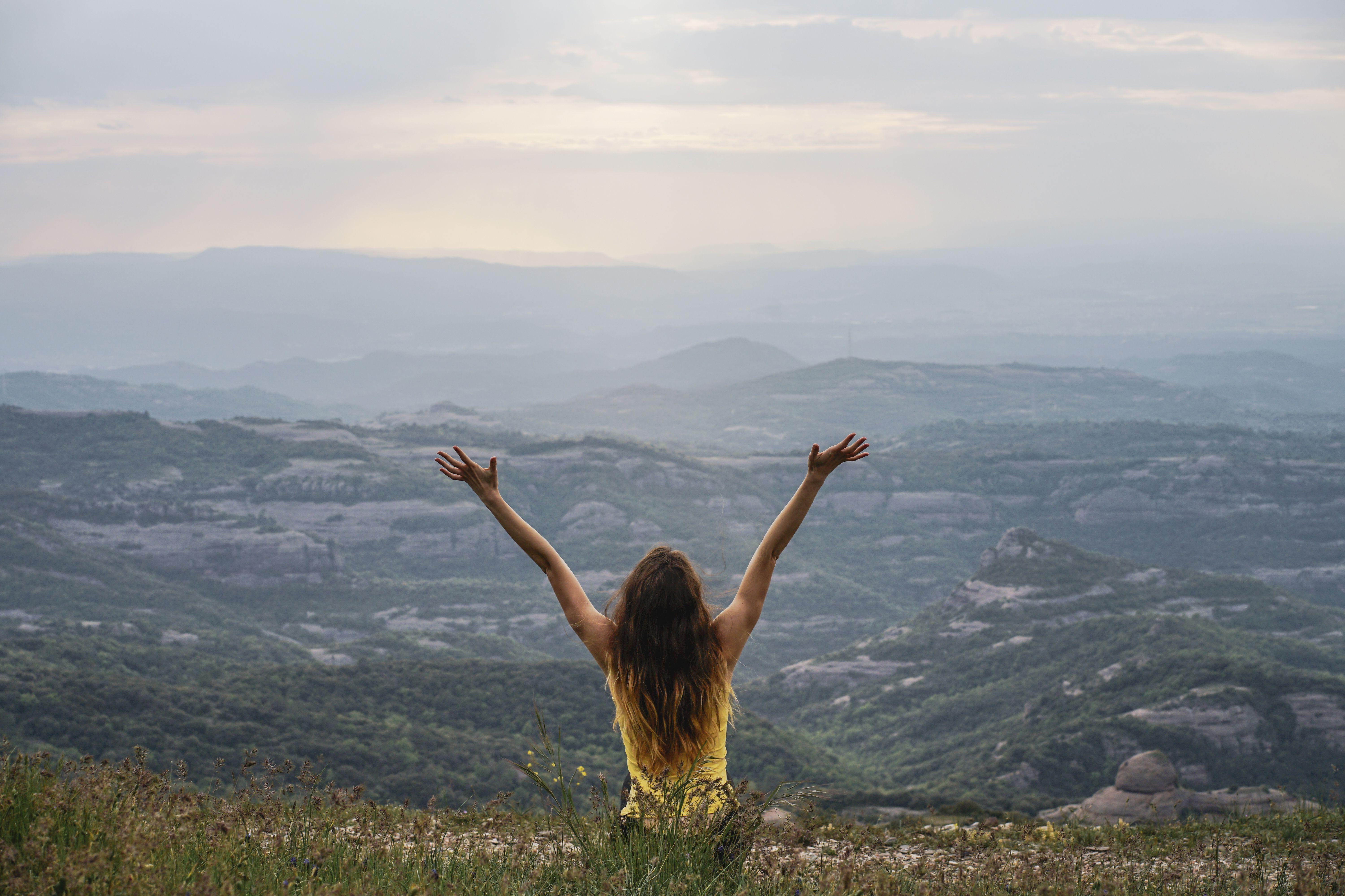 back view of happy young woman on a mountain
