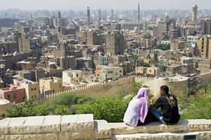 A couple sits on a wall overlooking the Al Azhar area, Islamic Cairo, Cairo, Egypt, North Africa, Africa