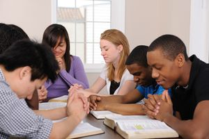 A group of young adults studying the Bible and praying together.