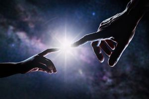 Hands touching on a background of a universe
