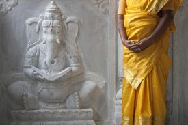 A woman stands next to a carving of Ganesha