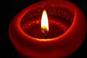 Close-up of illuminated red candle.