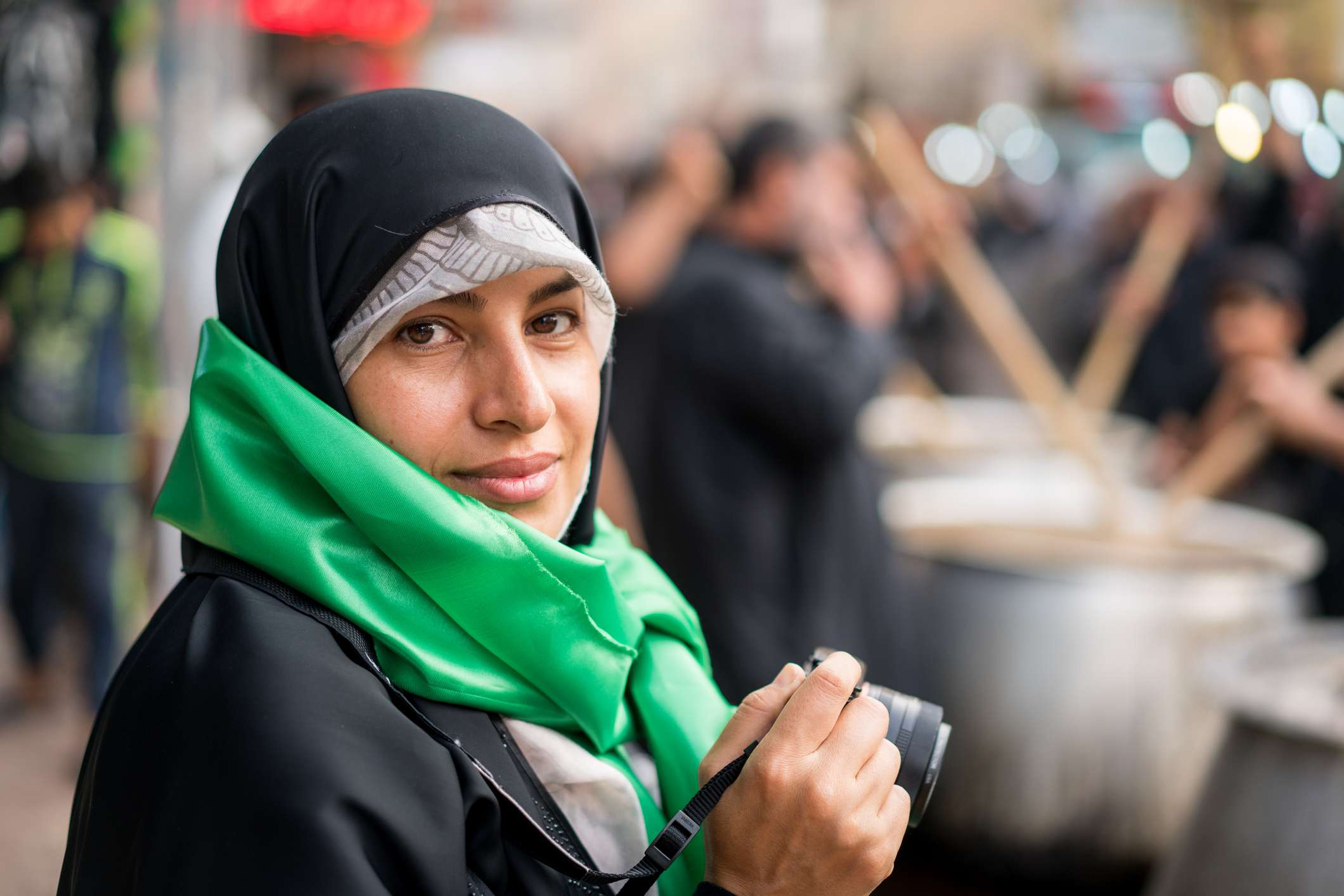 Middle Eastern woman on the street using camera for taking images