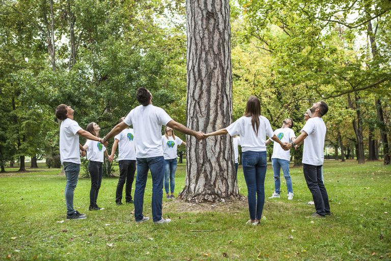 Teenage volunteers standing in circle round tree