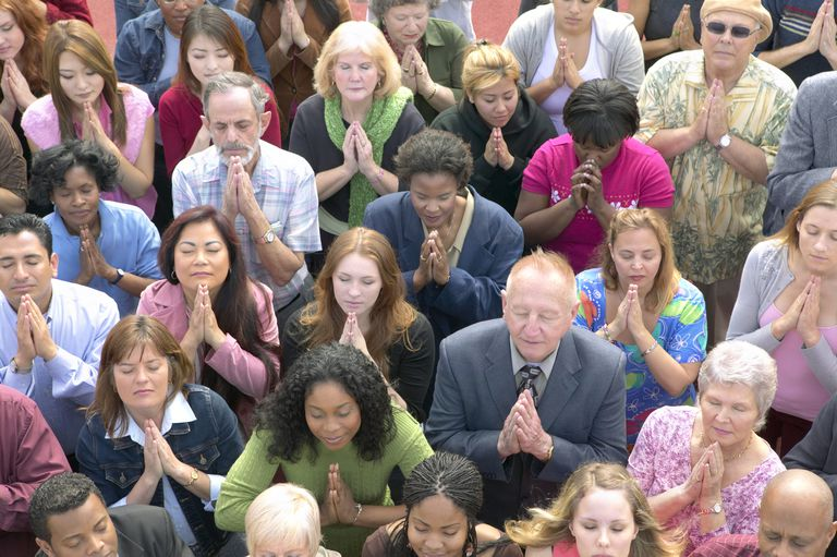 A diverse group of people praying