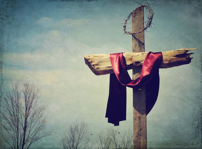 A red sash and crown of thorns hanging from the Christian Cross
