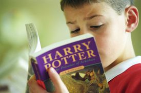 Boy reading a Harry Potter softcover book