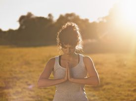 A young woman doing yoga in a field