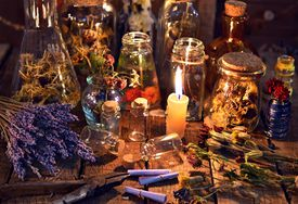 Bottles with herbs, lavender flowers, paper scrolls and magic objects