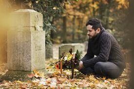 Man crouching at gravestone with flowers