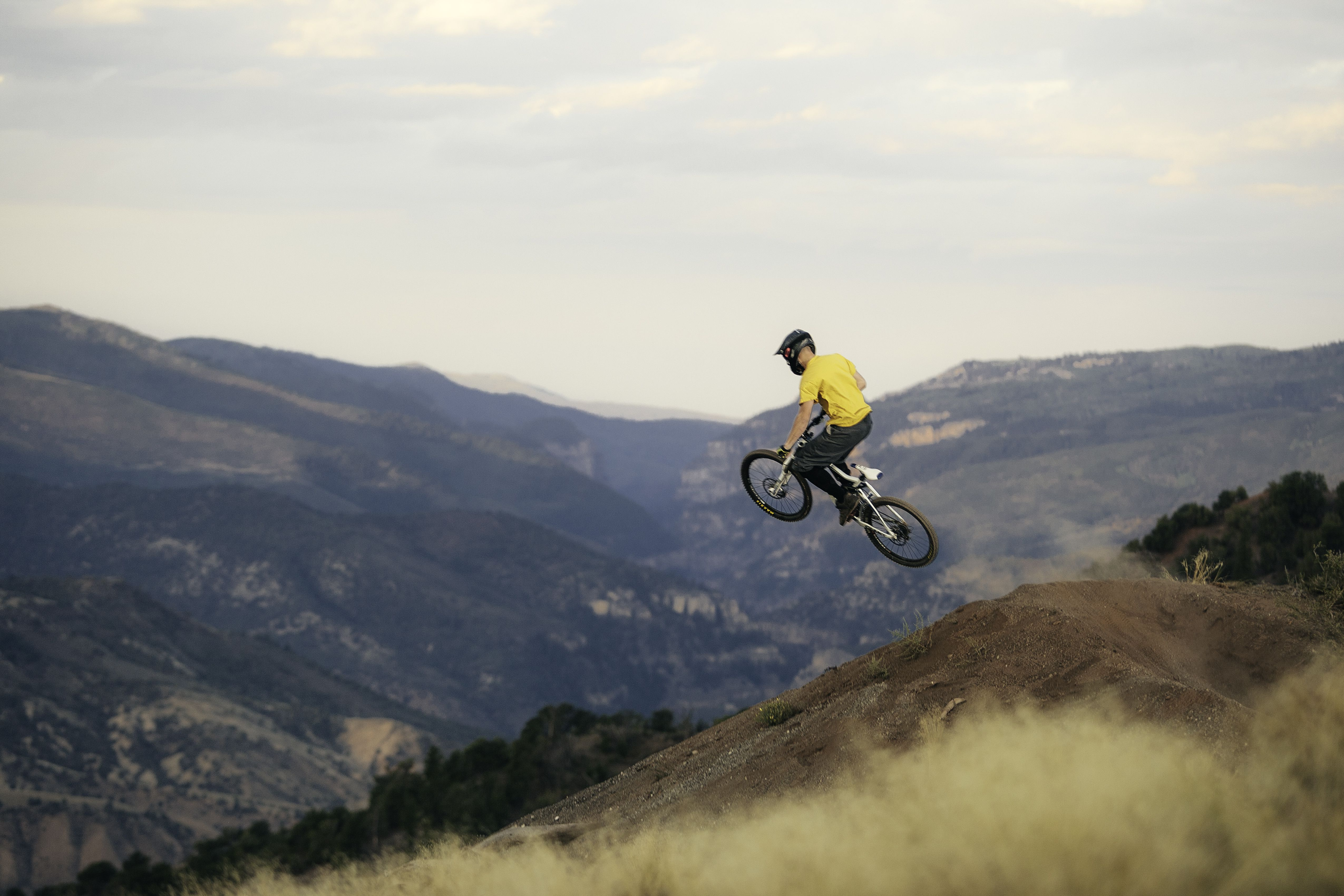 Guy with a mountain bike, jumping off of a jump.