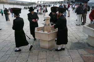 Four orthodox men washing their hands before shabbat prayers