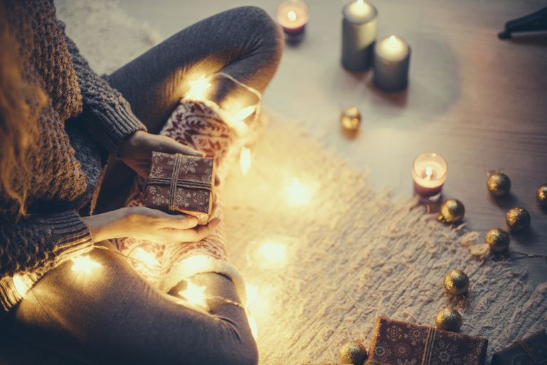 Woman sitting with Christmas present and fairy lights on the carpet