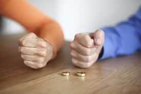 Clenched fists of couple next to gold wedding rings