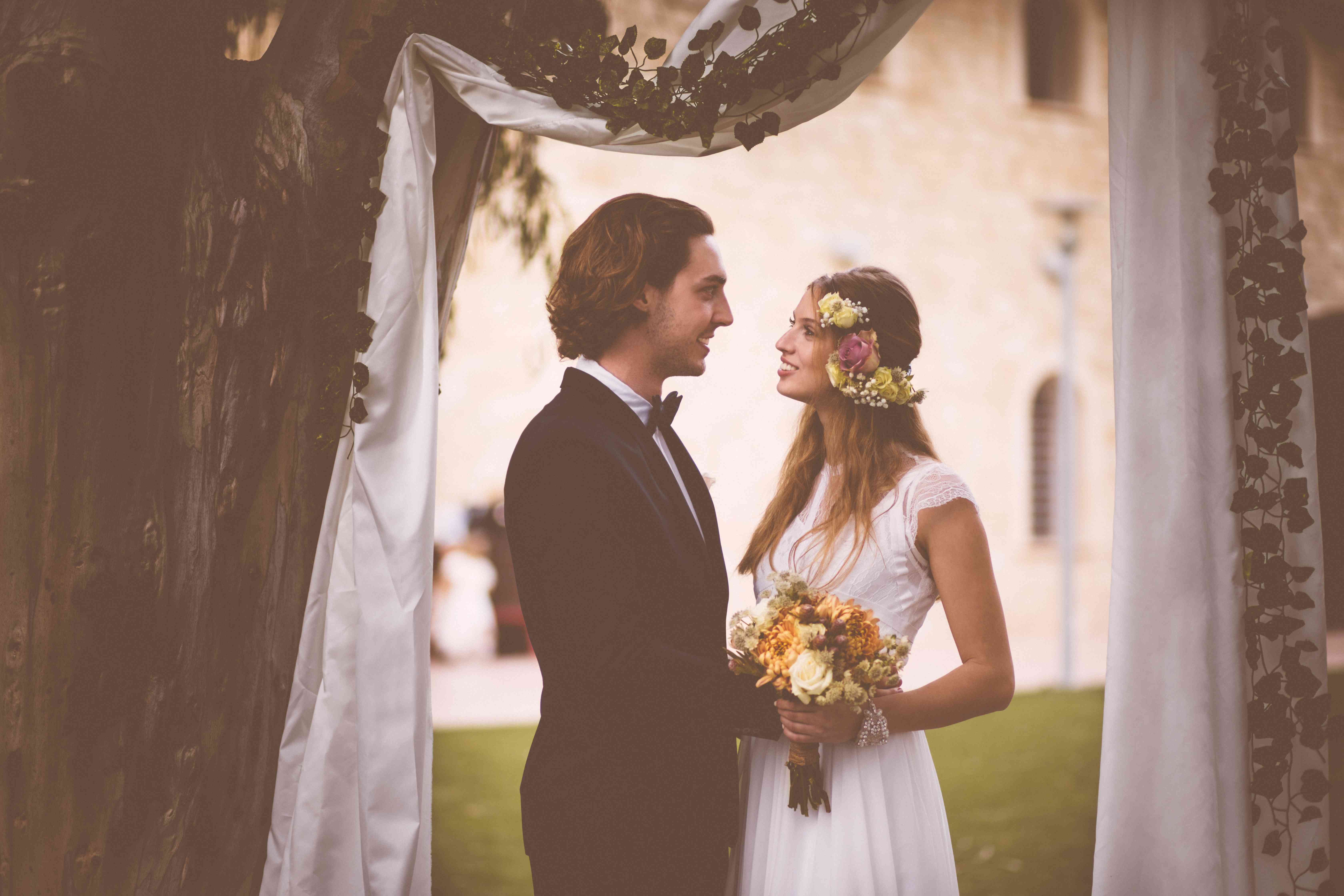 Bride and groom standing together at beautiful garden wedding ceremony