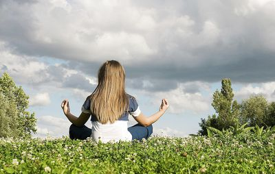 Girl meditating in clover field