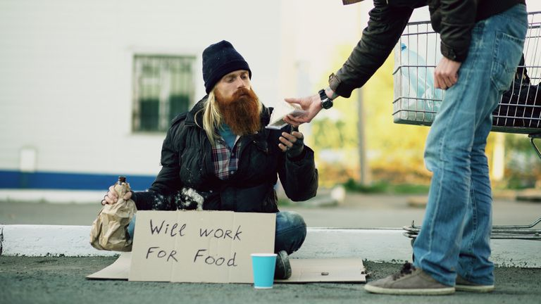 Young man helps homeless person by giving him some food.