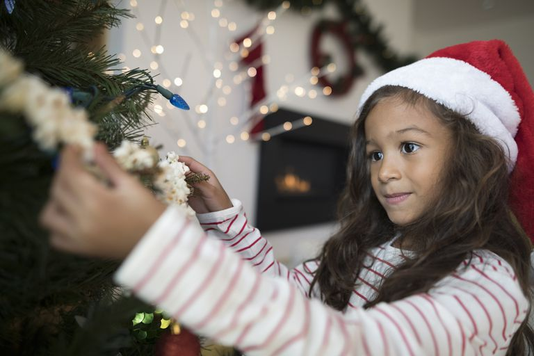 Focused girl in Santa hat hanging popcorn string decoration on Christmas tree