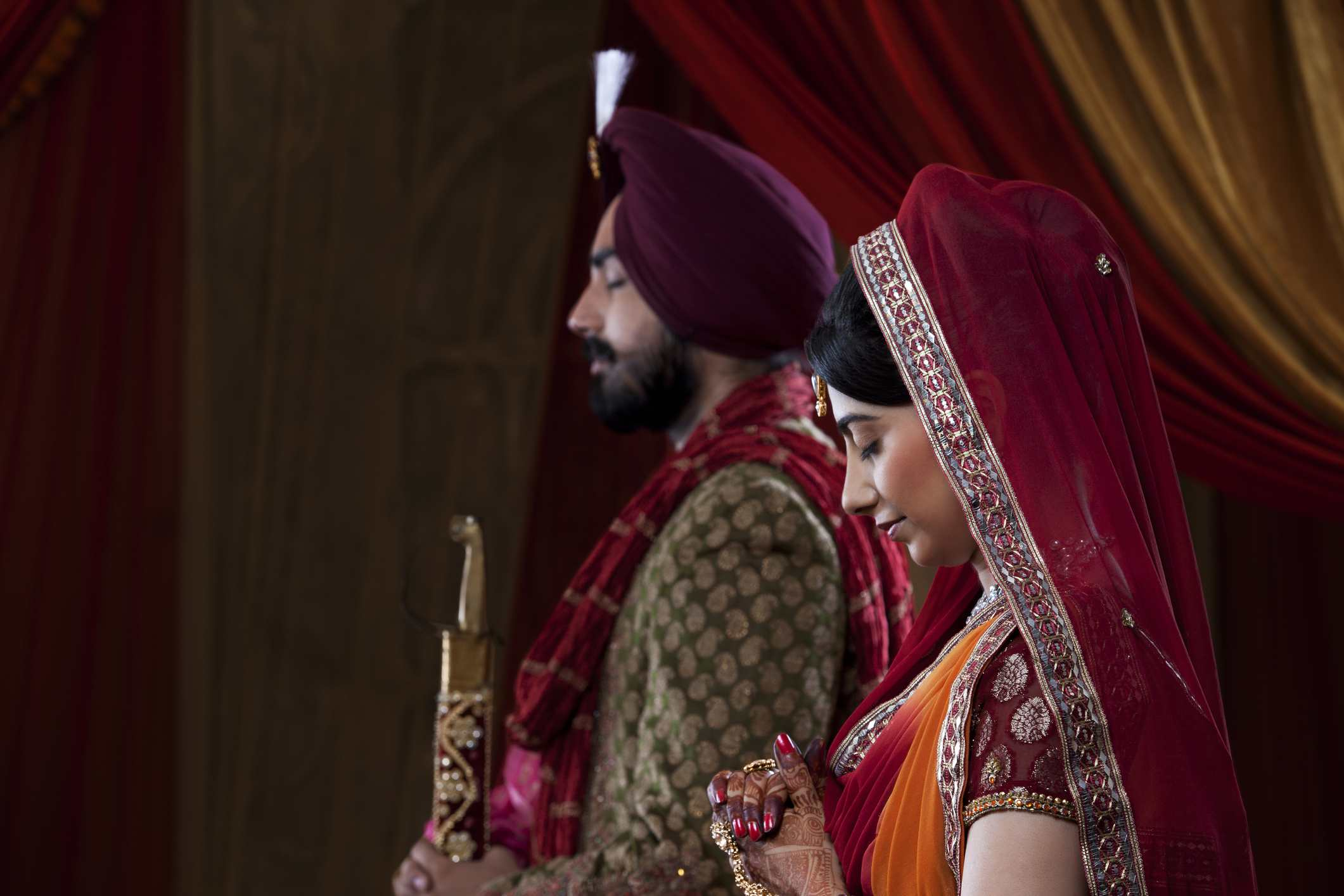 Sideview of Sikh couple praying