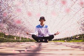 Young man meditating outdoors.