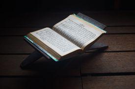 High Angle View Of Koran With Rehal On Hardwood Floor