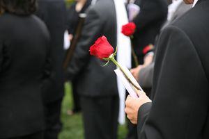 man holding a rose at a funeral