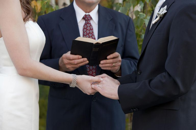 a couple holding hands with a pastor officiating at a wedding ceremony
