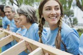 Young woman looking away while lifting wooden frame with volunteers