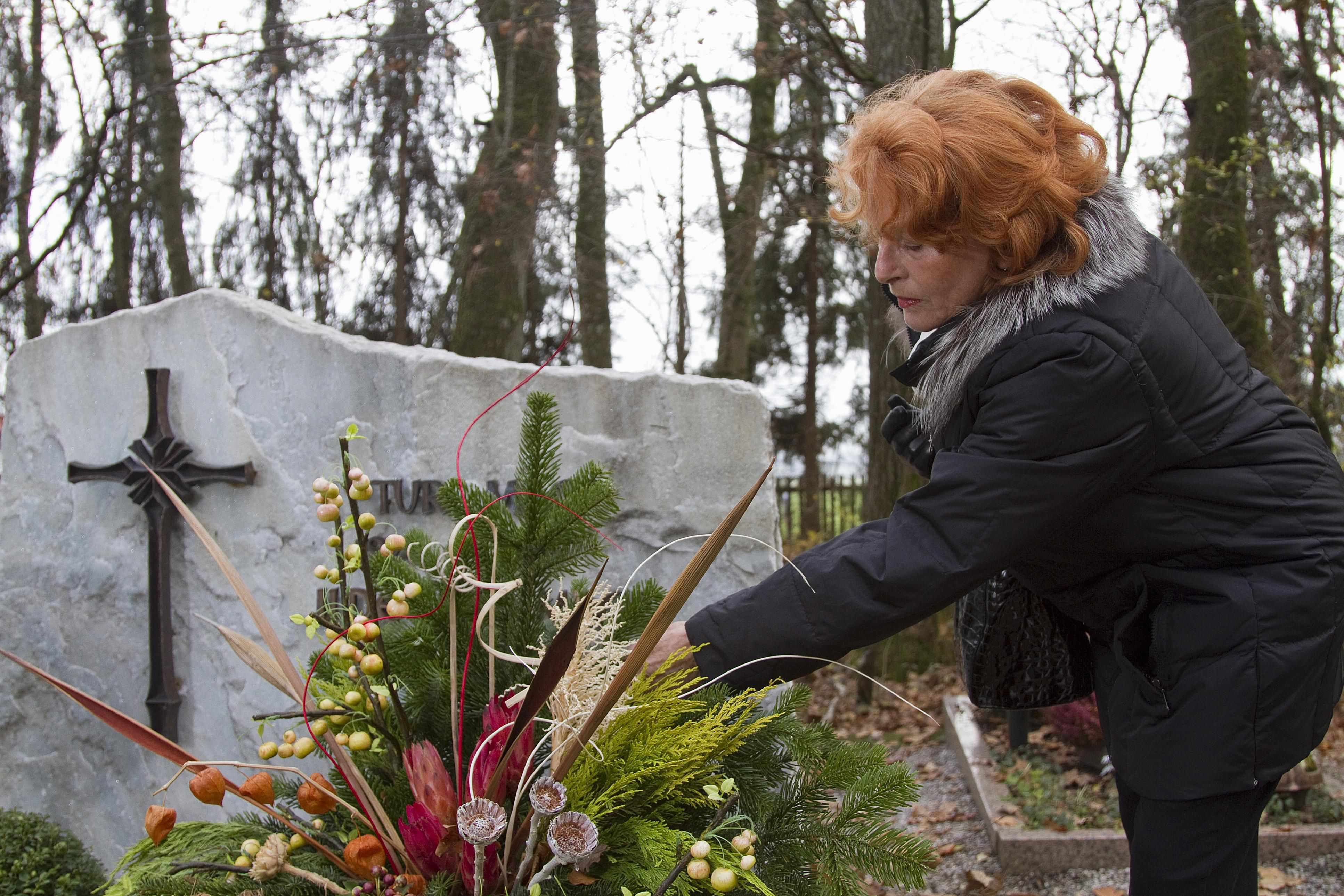 Woman placing flowers on a grave.