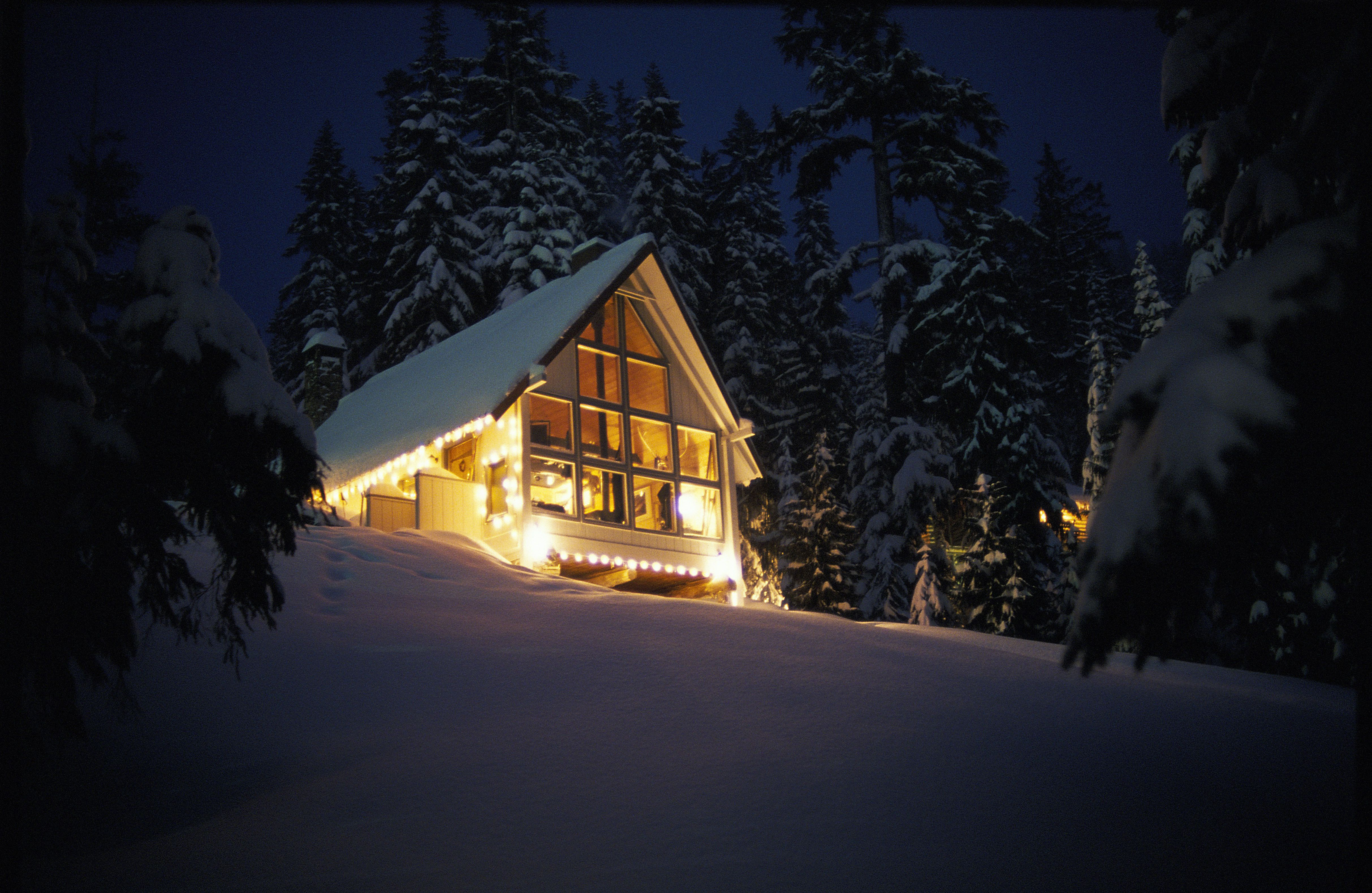 Cabin on top of hill in snow covered landscape at night